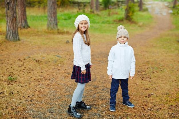 Irmão e irmã andando na bela floresta