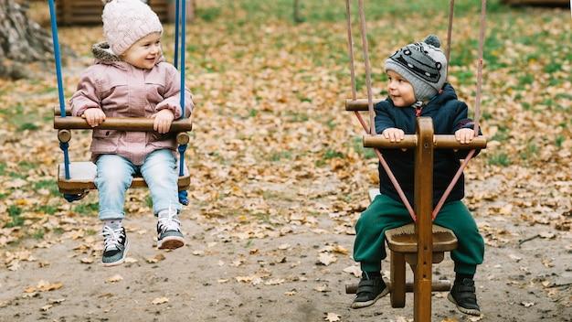Irmão e irmã balançando no parque