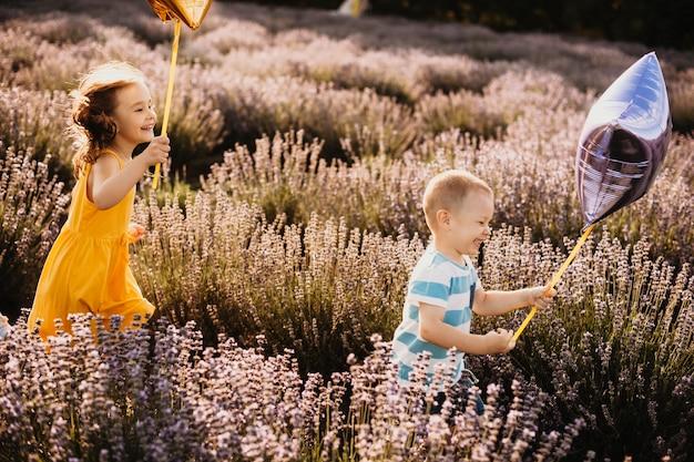 Irmão e irmã brincando com balões correndo em um campo de flores