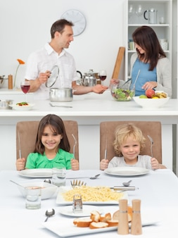 Irmão e irmã brincando com garfos enquanto cozinham seus pais