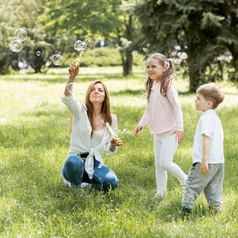 Irmão e irmã brincando com sua mãe
