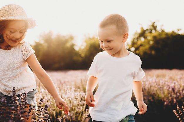 Irmão e irmã brincando em um campo de flores contra o pôr do sol. doce garotinho se divertindo com sua irmã.
