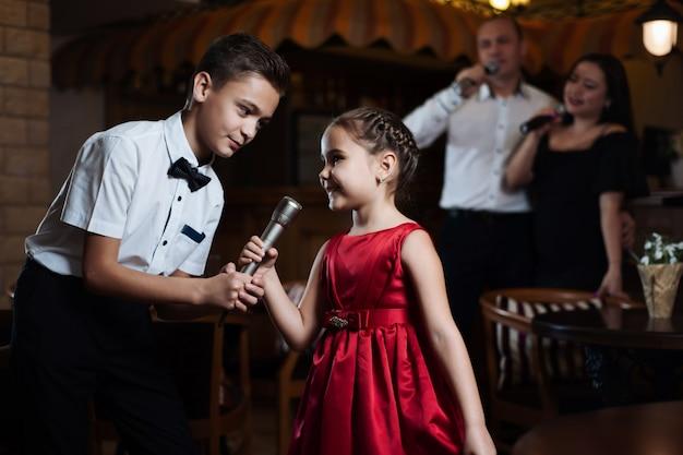 Irmão e irmã cantam músicas de karaokê em microfones, e seus pais cantam nas costas