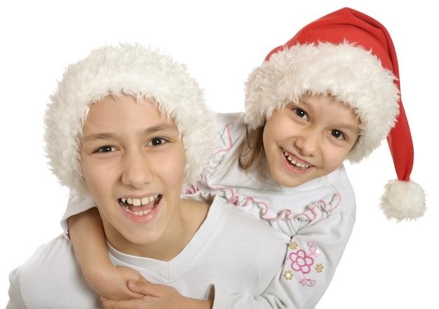 Irmão e irmã com chapéus de natal se abraçando