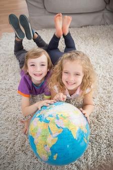 Irmão e irmã com globo sobre o tapete