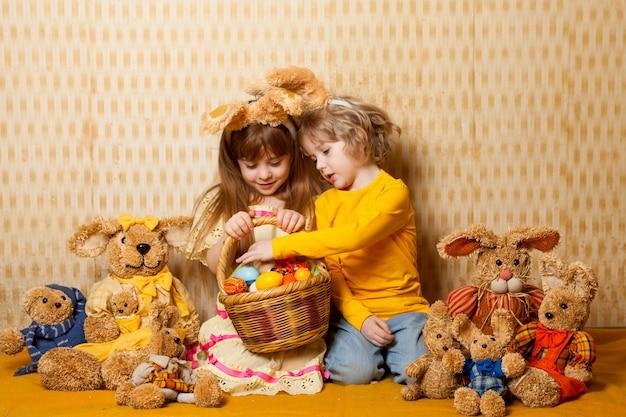 Irmão e irmã com orelhas de lebre e lebres de brinquedos estão sentados com uma cesta cheia de ovos de páscoa. férias em família em casa.