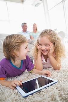 Irmão e irmã com tablet digital no tapete