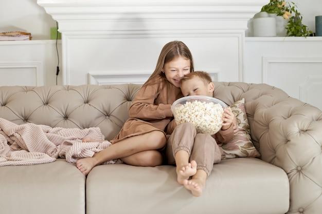 Irmão e irmã comendo pipoca sentados em casa no sofá. um menino e uma menina relaxam, se divertem e assistem um filme na tv