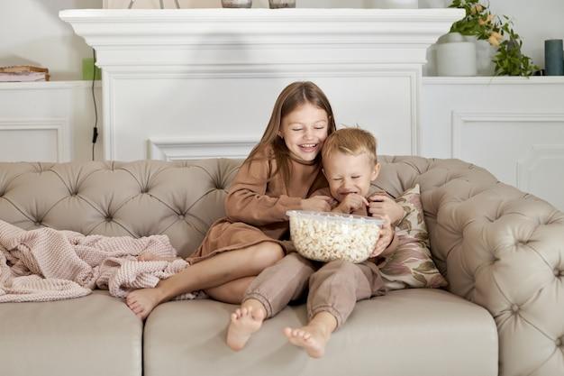 Irmão e irmã comendo pipoca sentados em casa no sofá