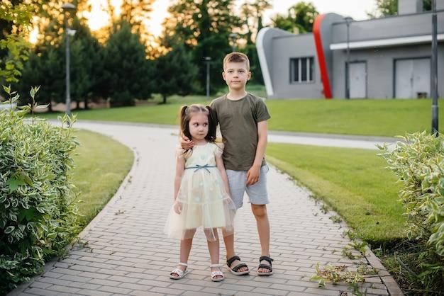 Irmão e irmã correm, brincam e se divertem no parque em um dia de verão durante o pôr do sol. infância feliz.