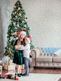 Irmão e irmã dão e desembalam presentes debaixo da árvore de natal, sentados junto à lareira, na manhã de natal.