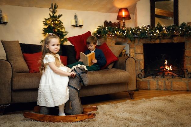 Irmão e irmã em antecipação ao ano novo passam um tempo na sala decorada com guirlandas
