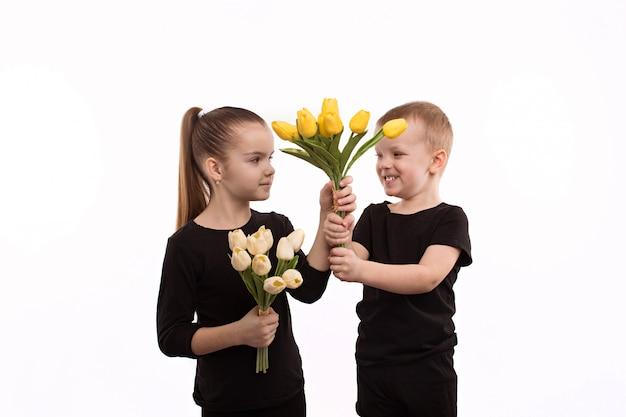 Irmão e irmã em blusas pretas segurando as tulipas nas mãos
