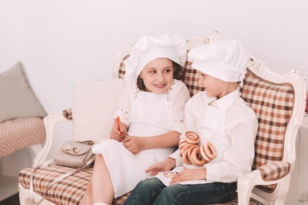 Irmão e irmã em bonés de chef discutem o menu do almoço