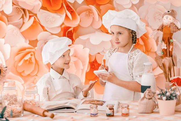 Irmão e irmã em chefs uniformes registram menu em pé na mesa da cozinha.