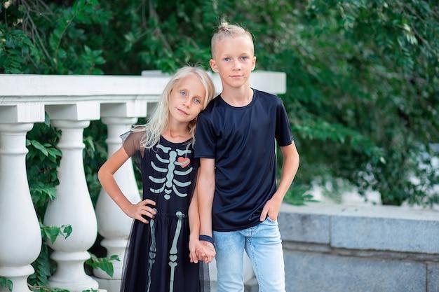Irmão e irmã em roupas pretas da moda segurando a alça