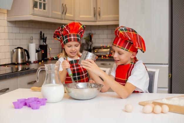 Irmão e irmã estão cozinhando biscoitos para o jantar festivo na cozinha conceito de inverno de ano novo