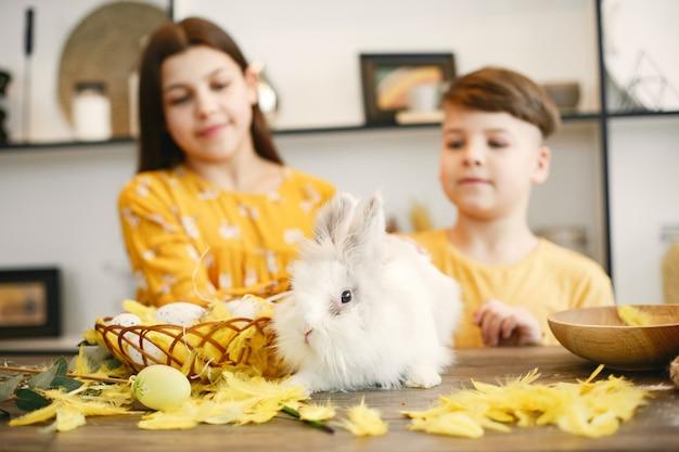 Irmão e irmã estão se preparando para a páscoa. menino e menina com roupas amarelas. as crianças recolhem uma cesta de páscoa.