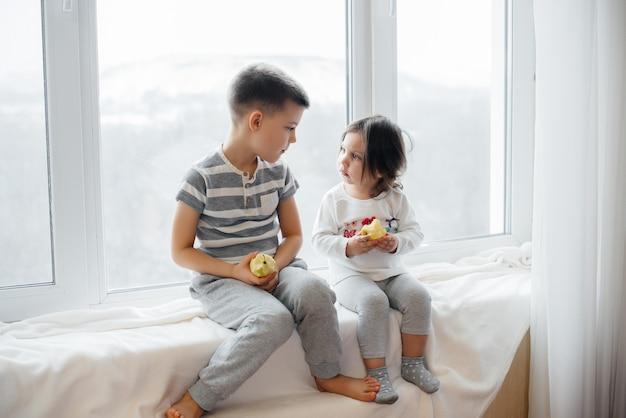 Irmão e irmã estão sentados no peitoril da janela, brincando e comendo maçãs.