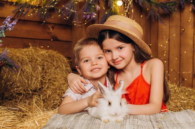 Irmão e irmã felizes abraçam um coelho na vila no feno conceito de férias da páscoa e família feliz