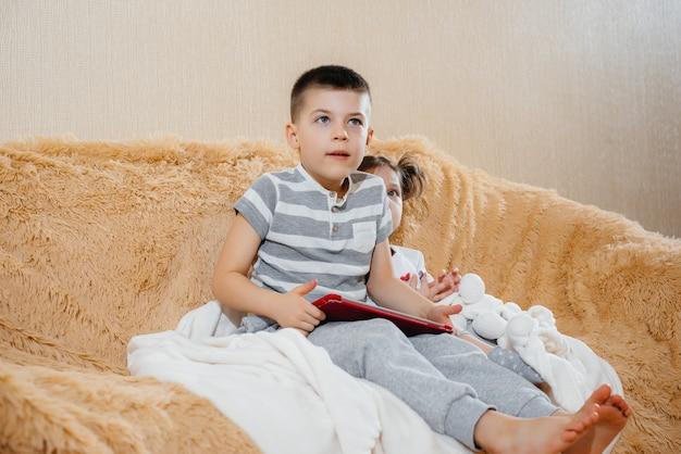 Irmão e irmã jogam no sofá no tablet.