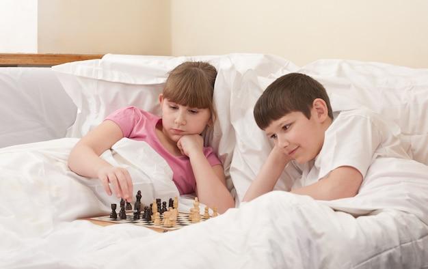 Irmão e irmã jogam xadrez na cama, dentro de casa
