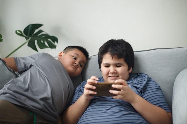 Irmão e irmã jogando em smartphones