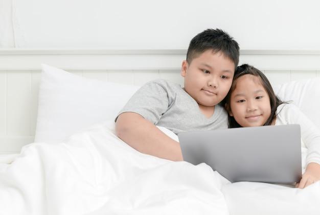 Irmão e irmã jogar laptop na cama juntos