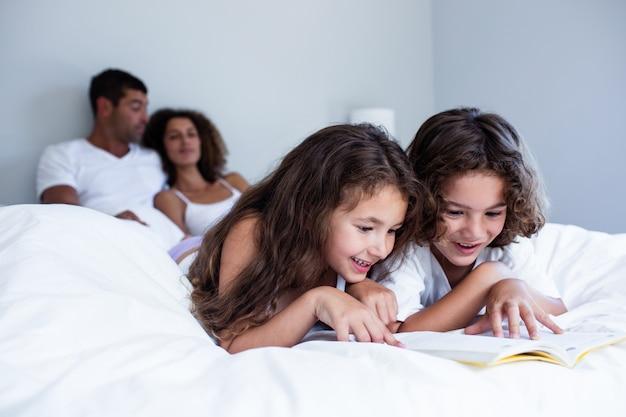 Irmão e irmã lendo livro juntos na cama