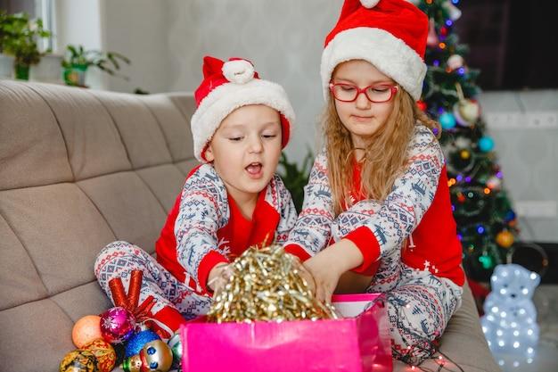 Irmão e irmã mais novos usando chapéus de papai noel no sofá contra a árvore de natal tiram enfeites da caixa