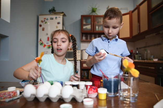 Irmão e irmã morenos decoram ovos de páscoa sentados à mesa em casa na cozinha
