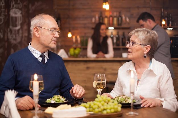 Irmão e irmã na casa dos sessenta anos curtindo o tempo juntos enquanto jantam em um restaurante vintage. homem e mulher felizes.