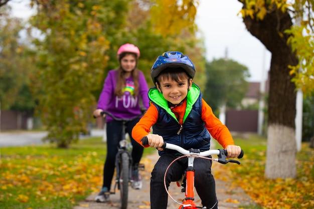 Irmão e irmã no parque. o menino aprende a andar de bicicleta sozinho.