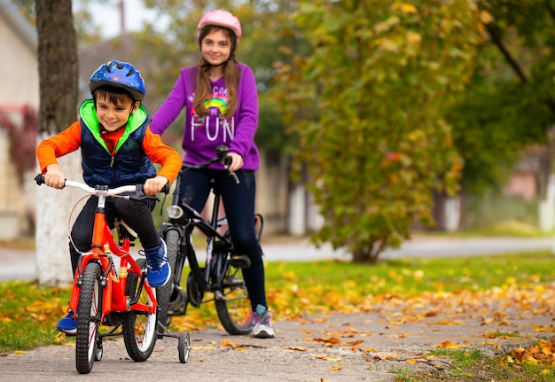 Irmão e irmã no parque. rapaz anda de bicicleta. foto com espaço lateral.