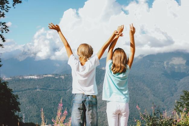 Irmão e irmã, olhando na vista maravilhosa do resort de montanha