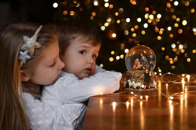 Irmão e irmã olhando para uma bola de vidro com uma cena do nascimento de jesus cristo