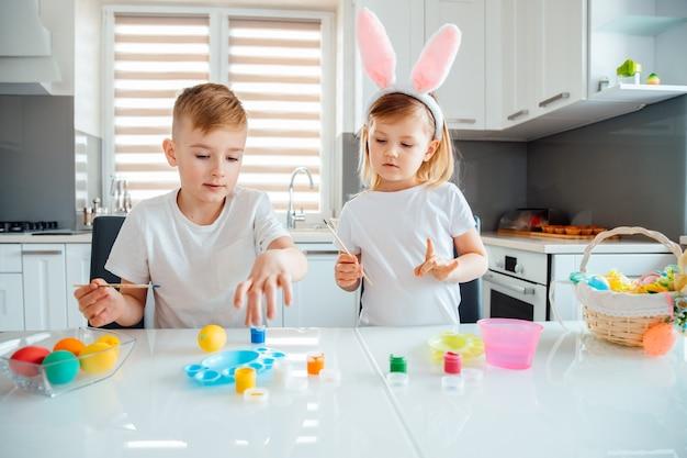 Irmão e irmã pintando ovos de páscoa.