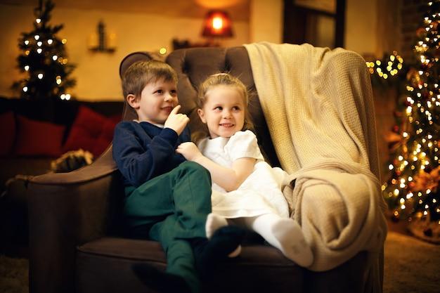 Irmão e irmã posando em uma poltrona em um aconchegante interior de natal com uma árvore de natal
