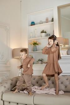 Irmão e irmã se divertem em casa e pulam no sofá. crianças dançam e ouvem música com fones de ouvido