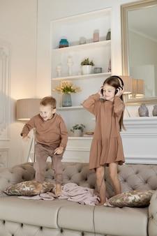 Irmão e irmã se divertem em casa e pulam no sofá