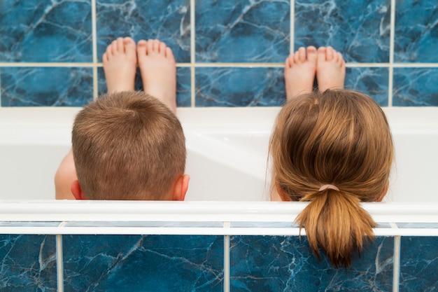 Irmão e irmã, tomando um banho de espuma. menino e uma menina brincando. conceito de cuidados de saúde e higiene.