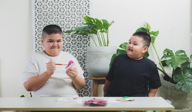 Irmão e irmão aprendem e realizam atividades em casa.