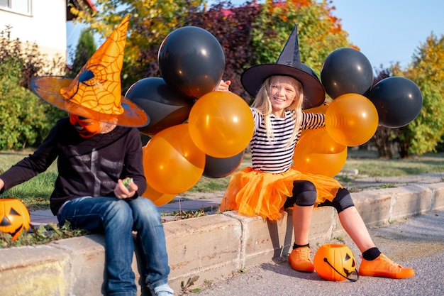 Irmão e irmãzinho fofos em fantasias de halloween