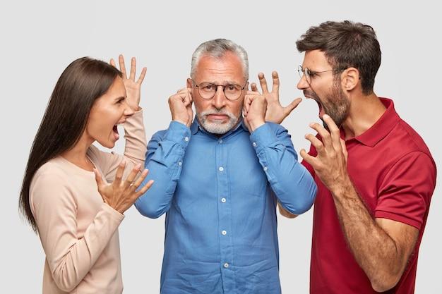 Irmão, irmã e pai idoso furiosos posando contra a parede branca