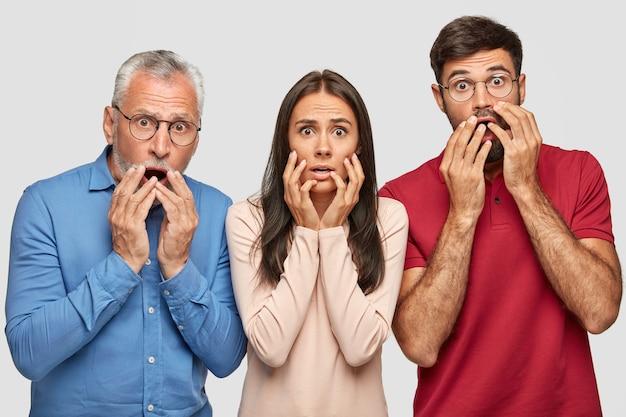 Irmão, irmã e pai idoso surpresos posando contra a parede branca