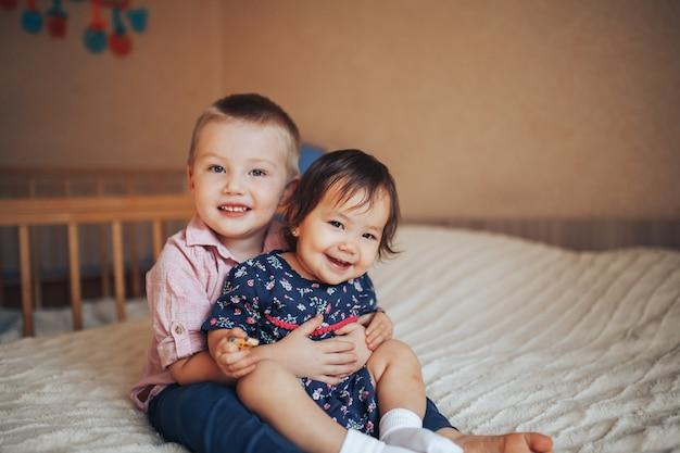 Irmão mais novo 3 anos e irmã 1 ano abraçando na cama