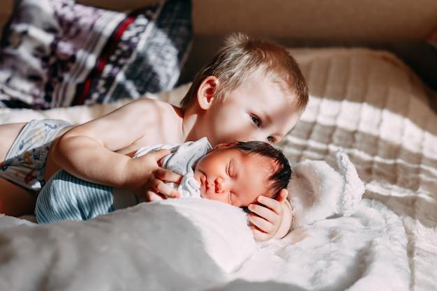 Irmão mais velho, beijando, irmã bebê recém-nascido