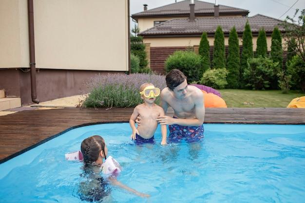 Irmão mais velho treinando irmão mais novo para nadar na piscina ao ar livre no verão estilo de vida saudável
