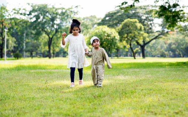 Irmão muçulmano e irmã brincando no parque