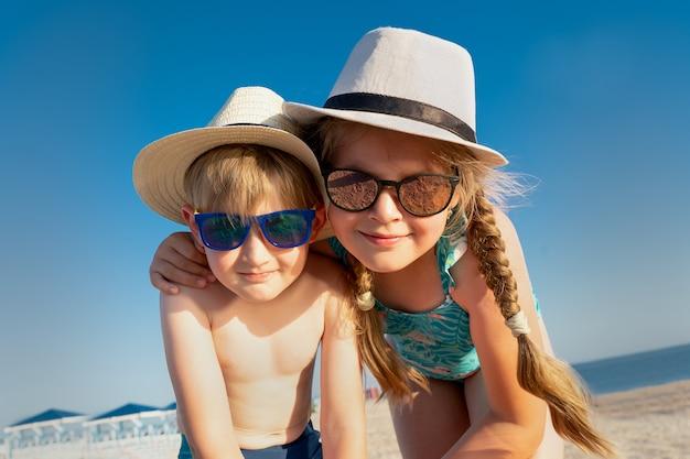 Irmão na praia. crianças de óculos escuros e chapéu de sol.
